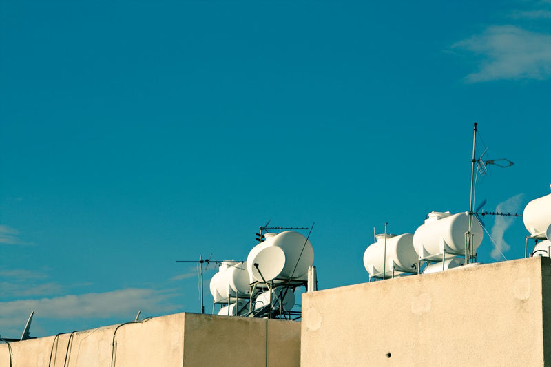 Low angle water tanks on rooftop against blue sky