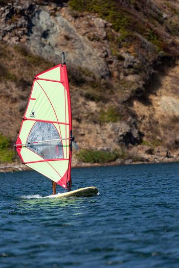 Sailboat in sea against mountain