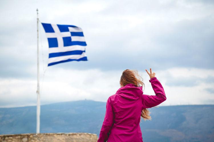 Woman Gesturing Towards Flag Against Sky