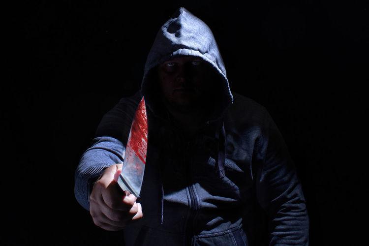 Portrait of criminal holding knife against black background