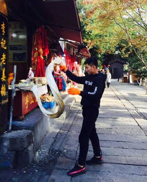 China Suzhou Local Food Street Food Food Making Sweets Chinese Culture Full Length Real People One Person Casual Clothing Building Exterior Outdoors Standing Architecture Day Built Structure Lifestyles Tree Men One Man Only Young Adult Adult City Adults Only People