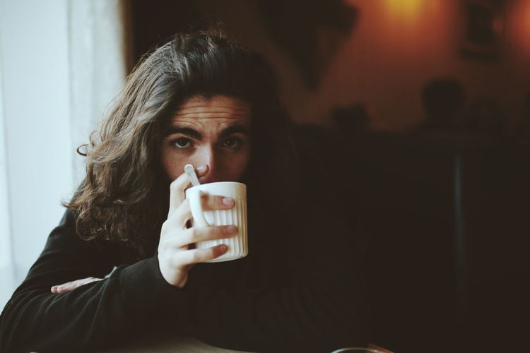 Portrait Of Man Drinking Coffee At Home