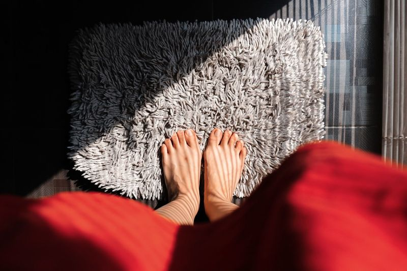 Low section of woman on doormat at home