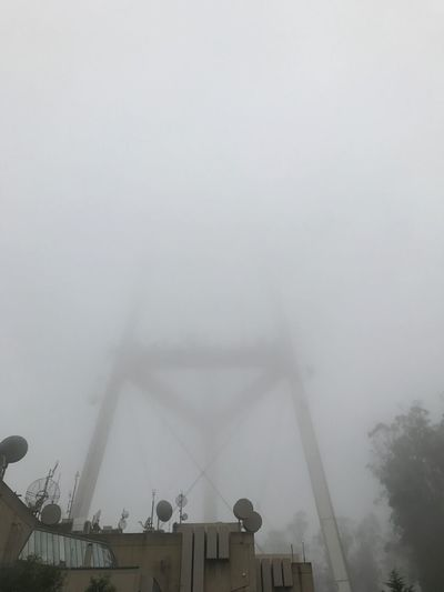 Low angle view of foggy weather against sky