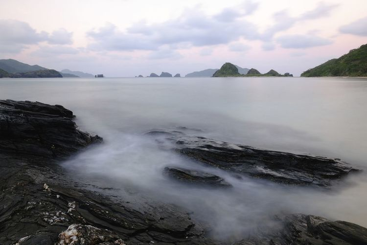 Stillness at dawn. Sky Cloud - Sky Water Beauty In Nature Scenics - Nature Tranquil Scene Sea Tranquility Rock Nature Non-urban Scene No People Rock - Object Solid Land Idyllic Beach Mountain Day Outdoors Zamami Sunrise
