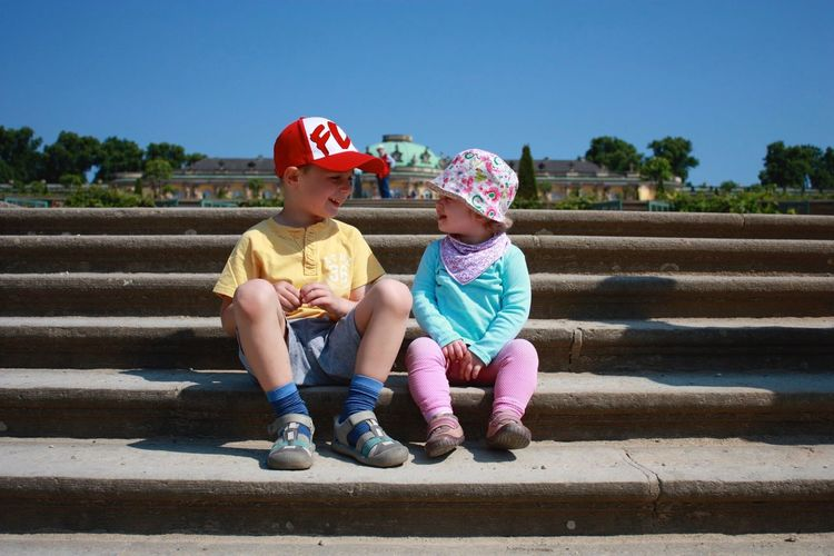 Full Length Of Cute Siblings Sitting On Steps During Sunny Day