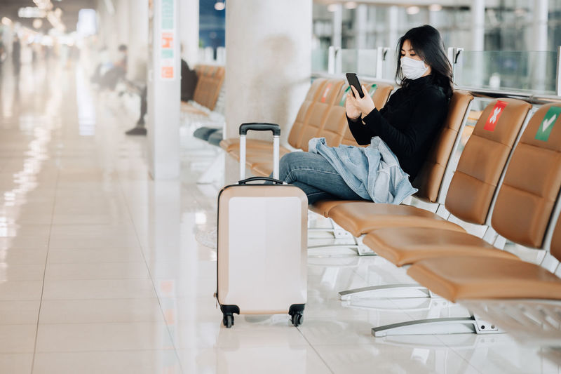 Woman wearing mask sitting on bench at airport