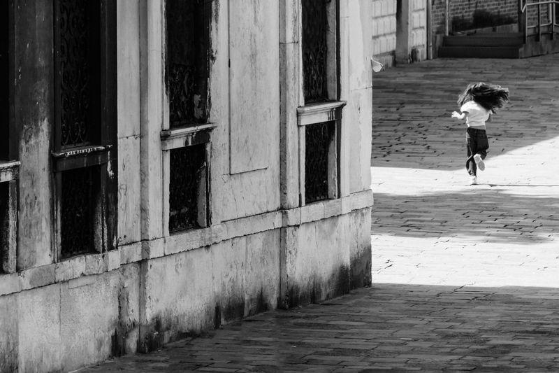 Rear view of woman walking on footpath by street in city
