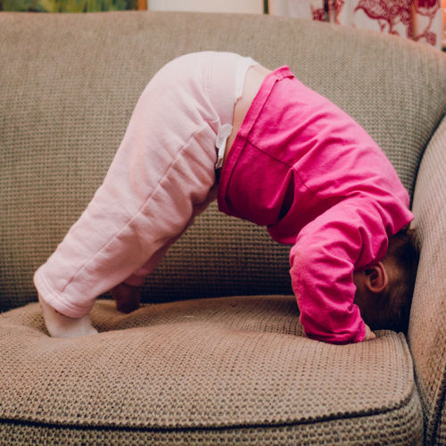 Side View Of Baby Girls Doing Headstand On Sofa At Home