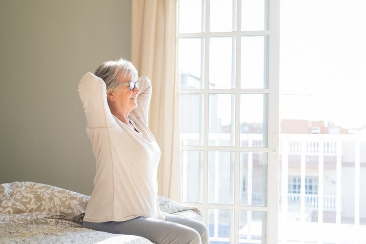Side view of woman sitting on window at home