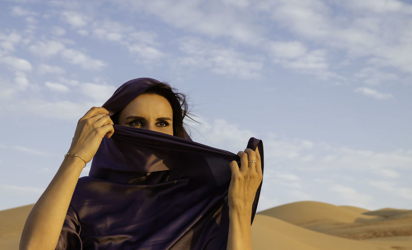 Woman wearing headscarf at desert against sky