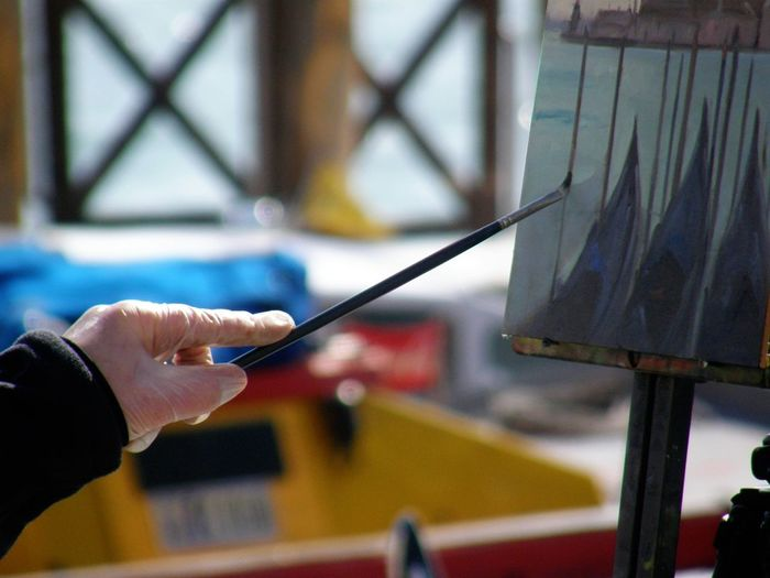 Cropped hand of painter painting on canvas outdoors