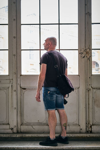 Adult Architecture Built Structure Casual Clothing Contemplation Day Full Length Hands In Pockets Jeans Leisure Activity Lifestyles Looking Looking Away Males  Men One Person Outdoors Real People Shorts Standing Window
