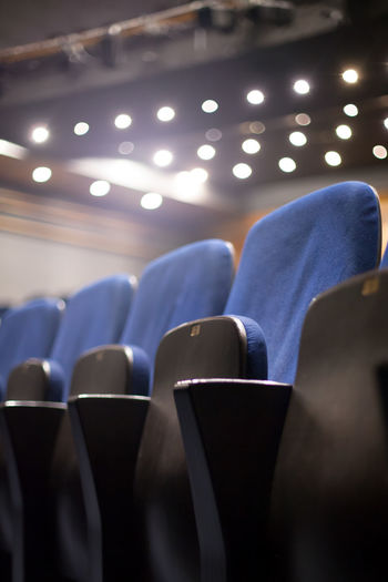 empty blue seats at the theater Theater Seats Empty Cinema Interior Inside Culture Arts Opéra Traditional Indoors  Entertainment Event Hall Public Amusement  Leisure Nobody Rows Lights Decoration Pattern Chair Row Seat Classical Comfortable Background Furniture Show Fancy Formal Stage Audience Film Auditorium MOVIE Performance Showtime Conference Many Detail Modern Side View Blurred Blue Vertical In A Row Absence