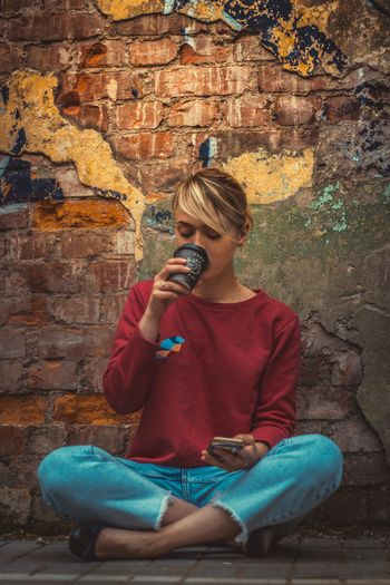 Mix Yourself A Good Time Sitting Leisure Activity Photography Themes Casual Clothing One Person Brick Wall Holding Real People Front View Lifestyles Outdoors Young Adult Young Women Blond Hair Wireless Technology Coffee Portrait