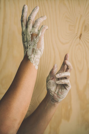 Close-up of woman with messy hands against wall