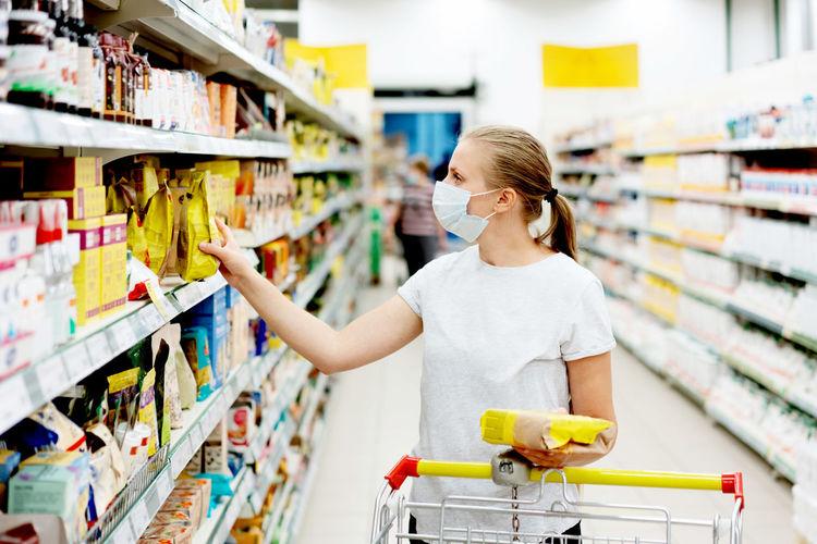 Woman wearing mask shopping in supermarket