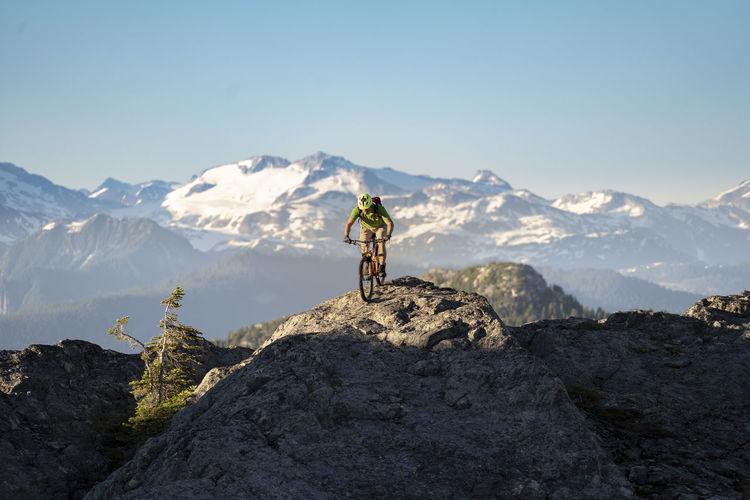 Man climbing on mountain against sky