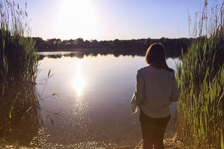 Rear view of woman standing in front of lake on sunny day