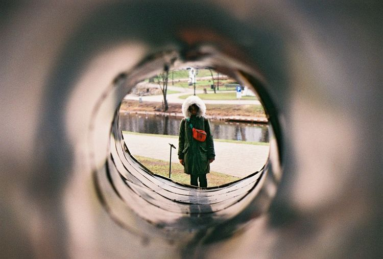 Woman in warm clothing seen through pipe