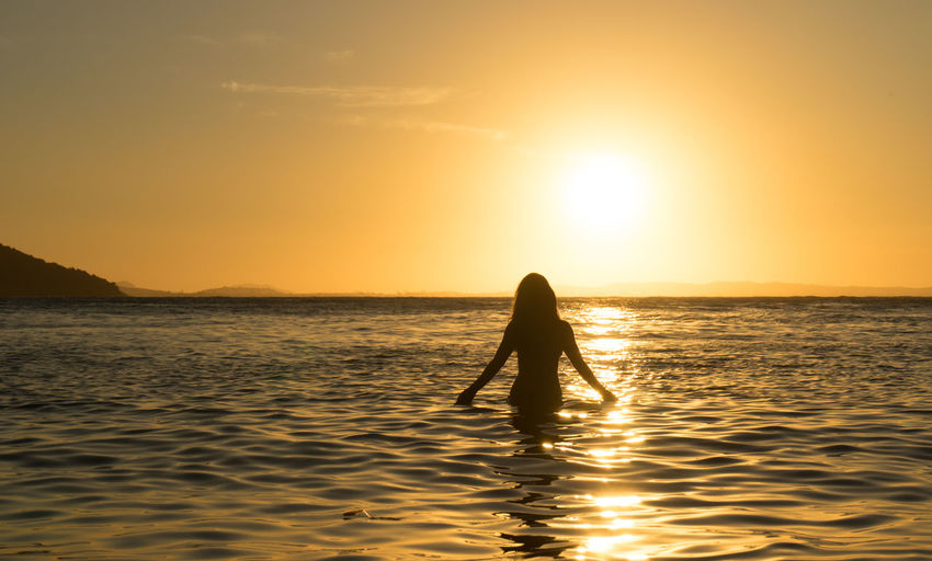 Silhouette of woman n sea at sunset