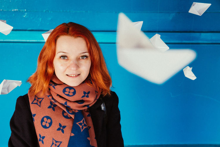 Smiling woman with paper boats hanging against blue wall