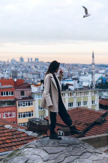 Woman standing by buildings against sky in city