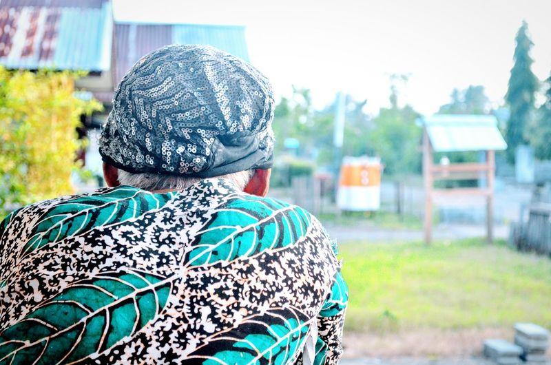 Rear view of woman wearing headscarf sitting in park
