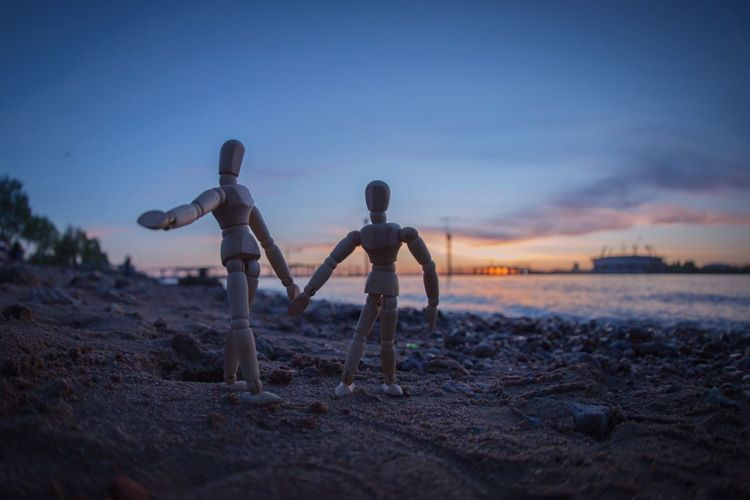Close-up of wooden figurines on beach against sky during sunset