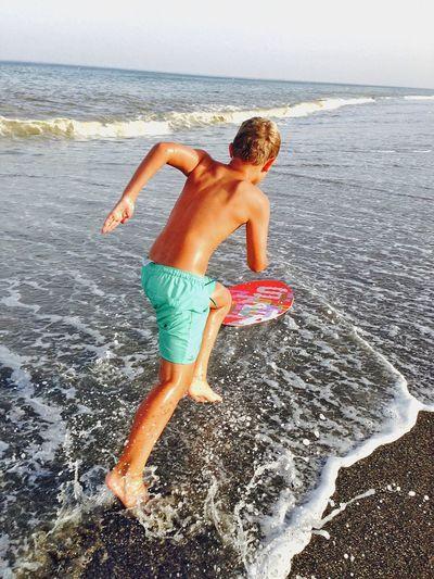 Shirtless Boy Running On Beach