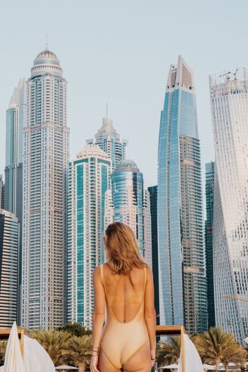 Rear view of woman wearing swimwear standing against modern buildings in city