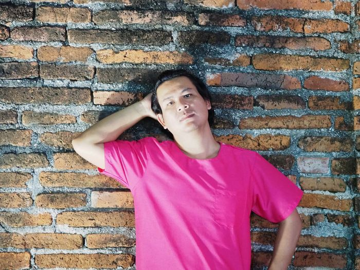 Close up portrait of asain man on brick wall background Man Asian  Portrait Pink Color Brick Wall