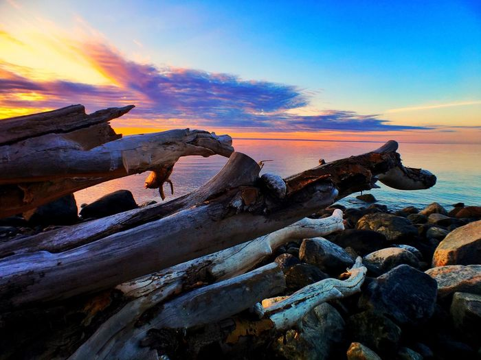 Seaside edit Sunset Sea Tranquil Scene Beach Sky Water Scenics Tranquility Wood - Material Shore Beauty In Nature Cloud - Sky Driftwood Nature Log Dead Plant Non-urban Scene Rocky Bonfire Outdoors Miles Away