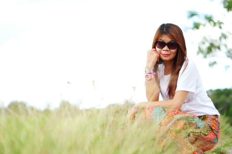 Portrait of woman in sunglasses on field