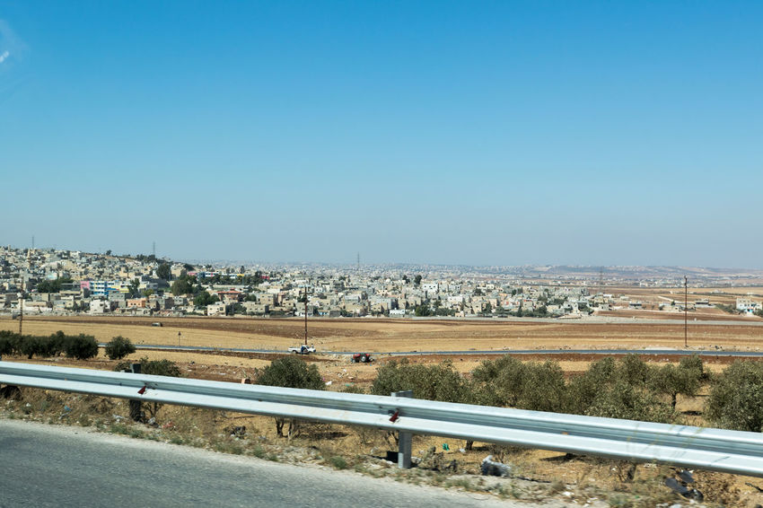 A distant view of a modern city in Jordan. Blue Bridge - Man Made Structure Cityscape Clear Sky Residential District Road Scenics Wide Shot