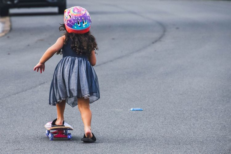 Rear view of girl with skateboard on street in neighbourhood