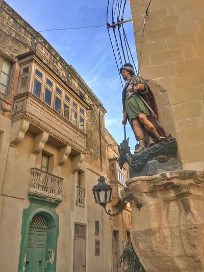 Low angla facade view in Victoria, Gozo Island, Malta Architecture Balcony Building Exterior Built Structure Day Full Length Low Angle View One Person Outdoors Real People Religious Art Sky Wooden Balcony Young Adult