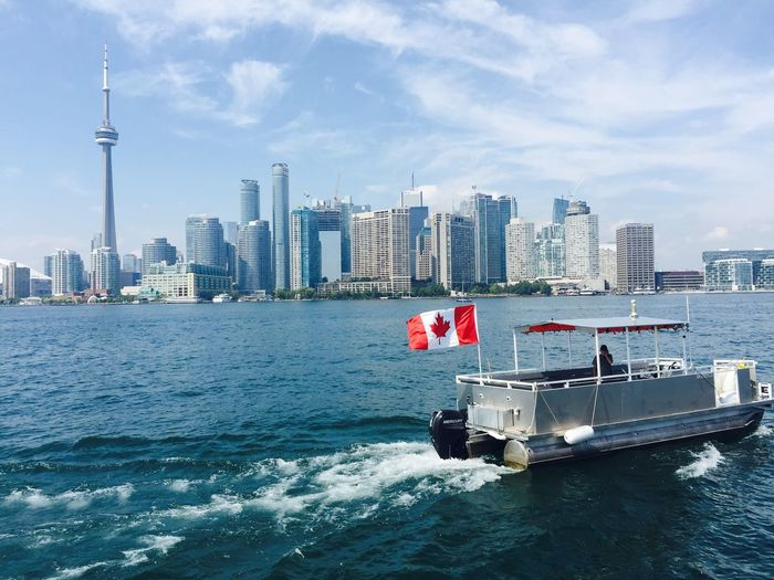 Boat With Canadian Flag Moving On Sea Against Cn Tower In City