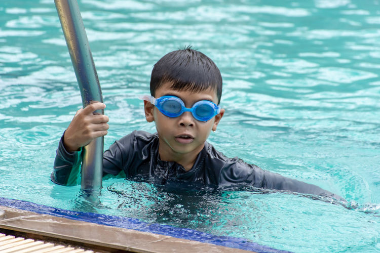 Asian boys are swimming in the pool. Childhood Child Pool Swimming Pool Water Boys Swimming One Person Swimming Goggles Portrait Males  Eyewear Swimwear Headshot Front View Leisure Activity Day Nature Innocence Outdoors