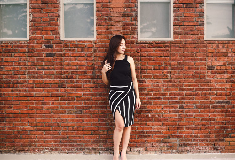 Young Woman Standing Against Brick Wall