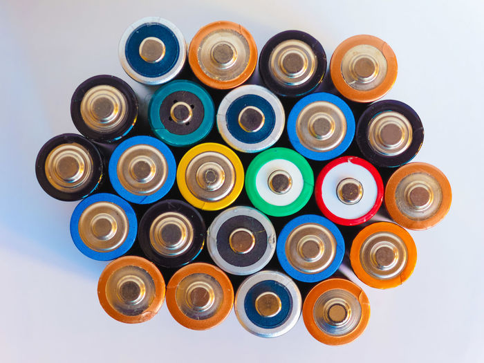 Directly above shot of multi colored batteries against white background