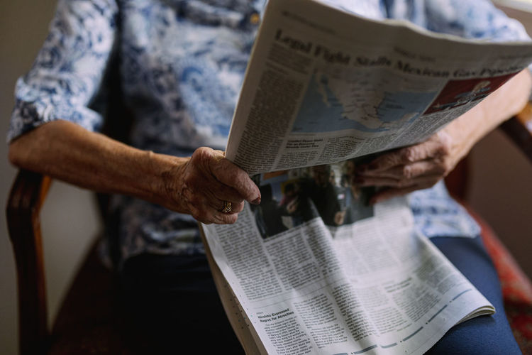 Midsection of senior woman reading newspaper at home