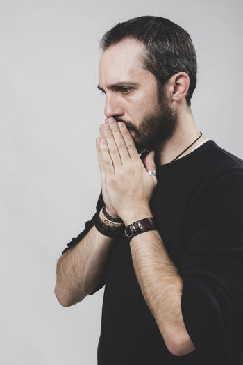 Bearded worried man on grey background. Contemplation Standing Young Men White Background Young Adult Facial Hair Beard Indoors  One Person Studio Shot Indoors  Front View Hand Gray Background Portrait Waist Up Gray Looking Casual Clothing Looking Away Hairstyle