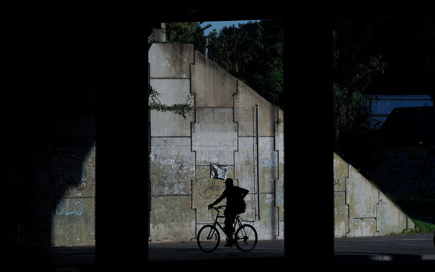 Silhouette man riding bicycle on building