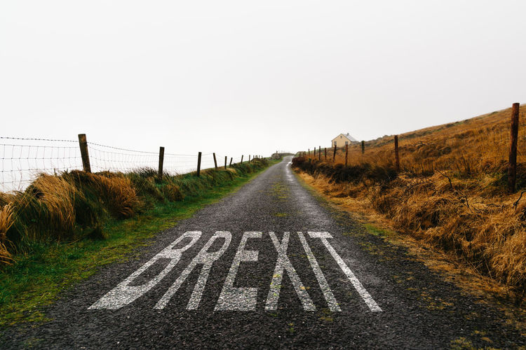 Concept of brexit. road marking with the word brexit painted on remote road a misty day.
