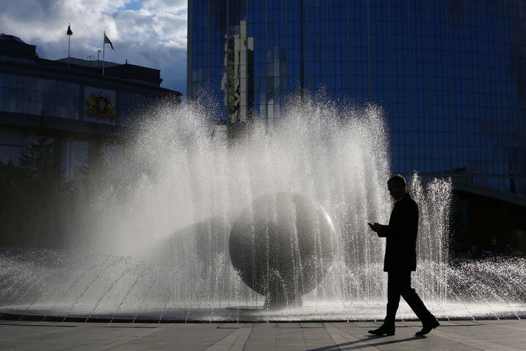 Man standing by fountain in city