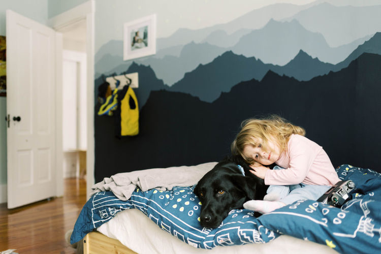 Woman with dog relaxing on bed at home