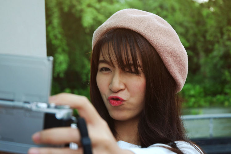 Playful Woman Puckering Lips While Photographing Through Digital Camera Outdoors