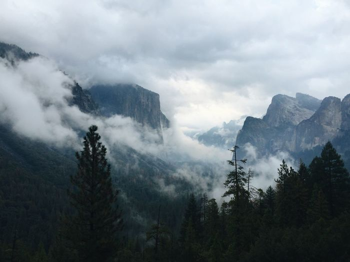 Scenic view of mountains against cloudy sky in foggy weather at yosemite national park
