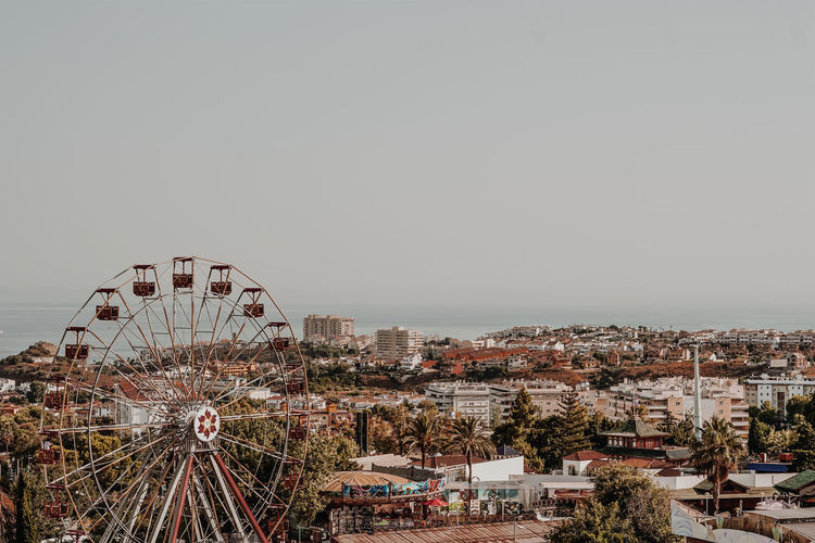 Ferris Wheel In City Against Clear Sky
